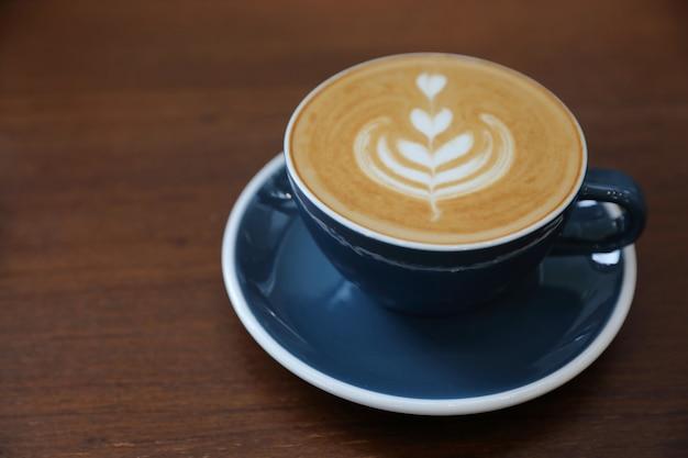 Café latte art feito com leite na mesa de madeira de uma cafeteria