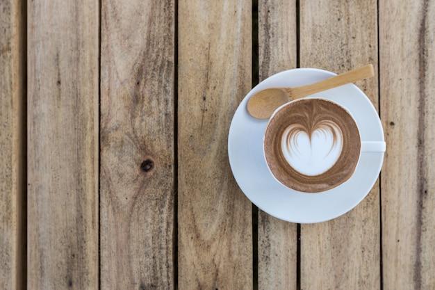 Café latte art na mesa de madeira
