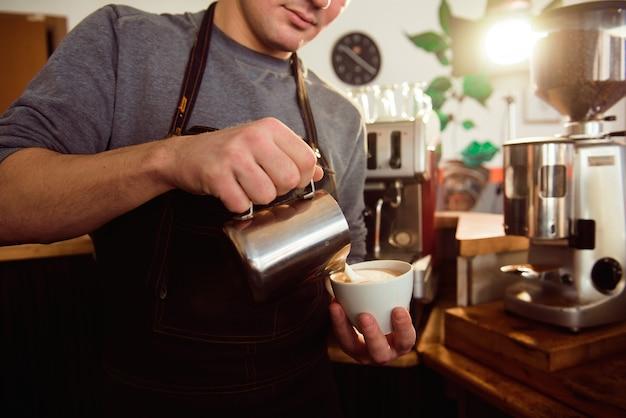 Café latte barista que faz o teste padrão em uma xícara de café.