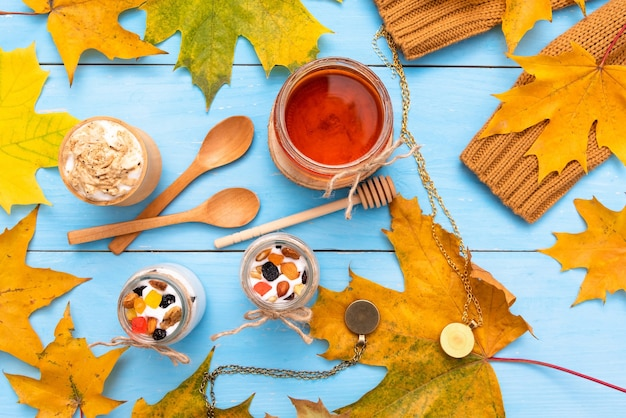 Café, mel e iogurte em uma mesa de madeira de outono.