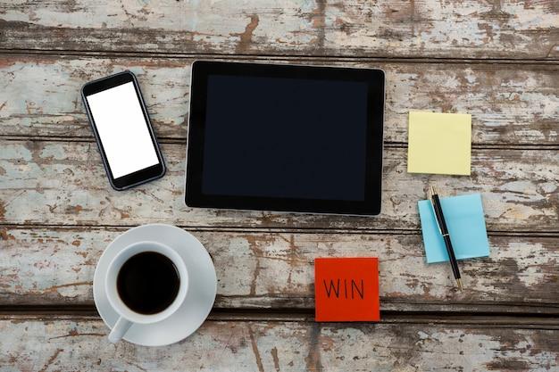 Café, mesa digital, smartphone e notas na mesa de madeira