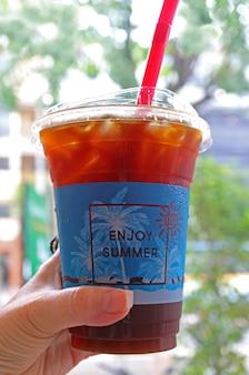 Café misto em copo de plástico para viagem na mão de uma mulher