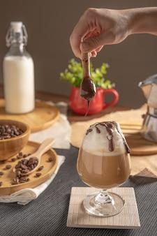 Café mocha gelado servido com cobertura de chantilly e calda de chocolate em taça de vinho, mesa de madeira