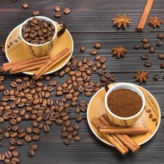 Café moído e grãos de café torrados em xícaras. paus de canela no pires. grãos de café e anis estrelado na mesa. fundo de madeira escura. postura plana