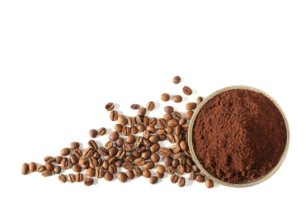Café moído em um pires de metal com grãos de café isolados na vista superior de fundo branco.