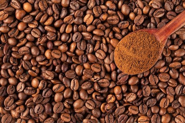 Café moído em uma colher vintage em grãos de café.