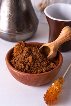 Café moído em uma tigela de madeira com palito de açúcar mascavo