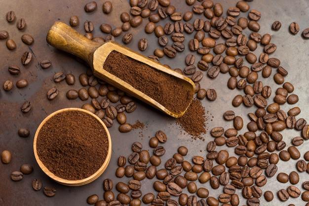 Café moído em uma tigela de madeira e na colher. grãos de café torrados na mesa.