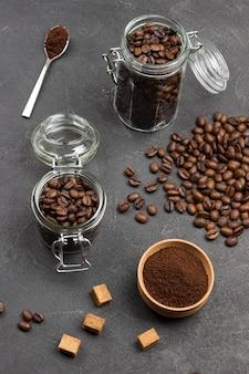 Café moído em uma tigela de madeira e uma colher. grãos de café torrados em jarra de vidro e em saco de papel. pedaços de açúcar mascavo na mesa. vista do topo.