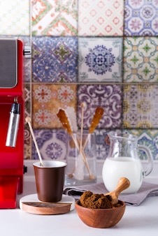 Café moído em uma tigela de madeira, máquina de café na bancada da casa