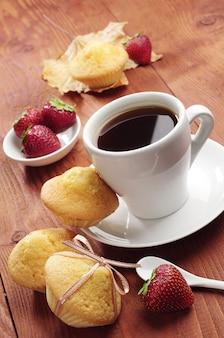 Café, morango e bolinho com laço na mesa de madeira