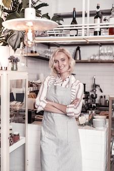 Café. mulher feliz e encantada em pé na cozinha enquanto trabalhava no café