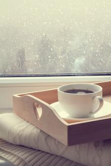 Café na bandeja e camisola em do inverno nevando