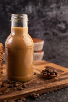 Café na garrafa com grãos de café em um prato de madeira.