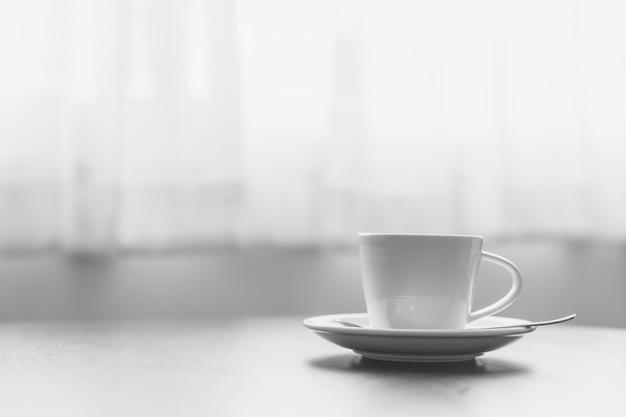Café na manhã, um copo do café na tabela de madeira no café ou no coffeeshop.