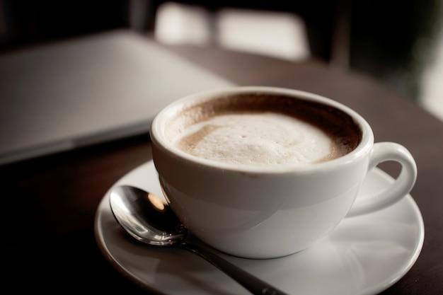 Café na mesa com o laptop a trabalhar no café, relaxar e conceito de tempo livre