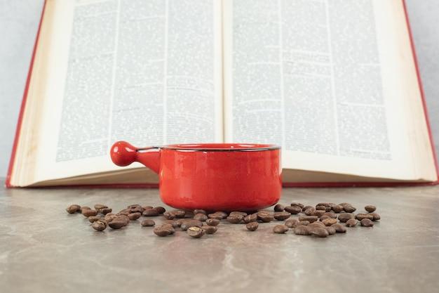 Café na superfície de mármore com grãos de café e livro