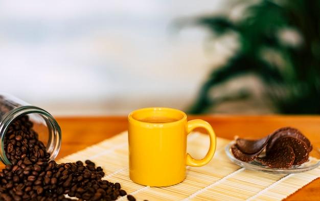 Café na xícara de cerâmica amarela e grãos de café na mesa de madeira - biscoitos de chocolate no fundo