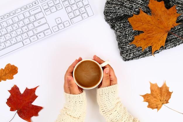 Café nas mãos em um desktop branco e teclado, folhas de outono. humor de queda.