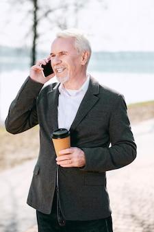 Café no parque. homem de negócios sênior otimista tomando café no parque e falando ao telefone