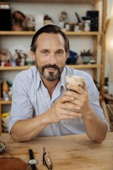 Café no trabalho. homem maduro e bonito sentado à mesa de madeira bebendo um café saboroso no trabalho