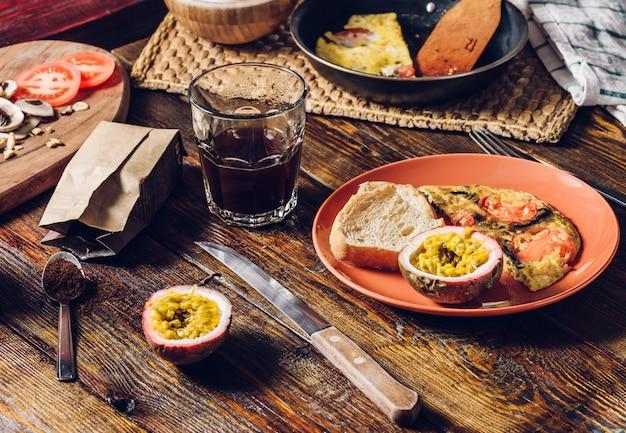 Café, omelete e granadilla no café da manhã