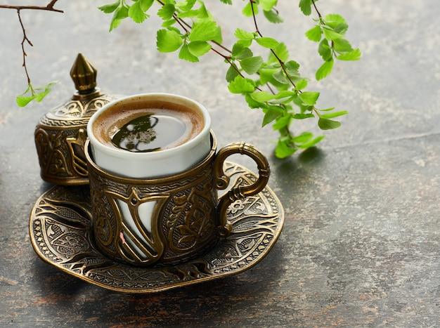 Café oriental cozido no bule de café de cobre tradicional turca derramado em um copo