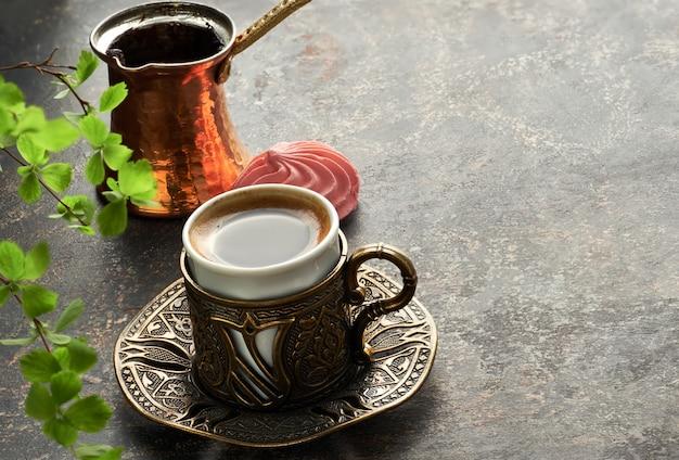 Café oriental cozido no bule de café de cobre turco tradicional derramado em um copo em uma mesa escura