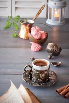 Café oriental cozido no bule de café tradicional de cobre turco e servido em uma xícara correspondente
