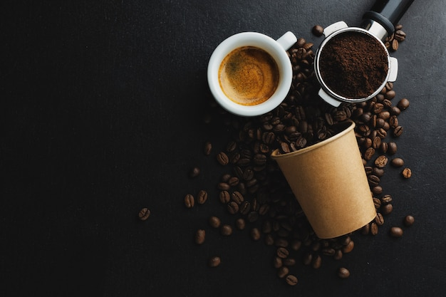 Café ou conceito de desperdício zero. grãos de café em copo de papel com uma xícara de café expresso em fundo escuro.