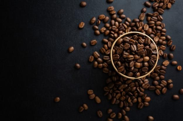 Café ou conceito de desperdício zero. grãos de café em copo de papel em fundo escuro.