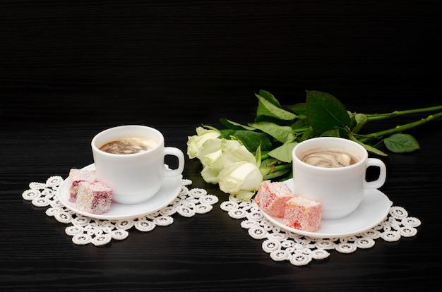 Café para dois com doces orientais, um buquê de rosas brancas em fundo preto