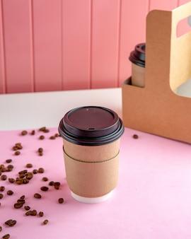 Café para viagem com grãos de café na mesa