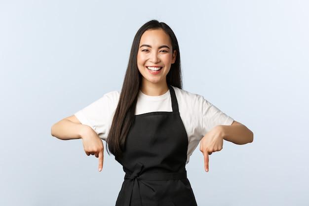 Café, pequena empresa e conceito de inicialização. barista asiática amigável alegre no avental preto, mostrando o anúncio. proprietária de um café bonito convidando para uma oferta especial, apontando o dedo para o banner
