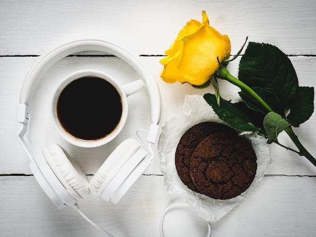 Café perfumado, biscoitos frescos, rosa e fones de ouvido