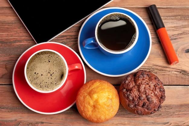 Café perto de muffins na madeira. batom e tablet vermelhos. cafeína e açúcar.