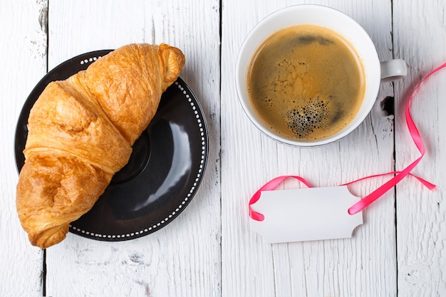Café postal vazio de croissant na mesa de madeira