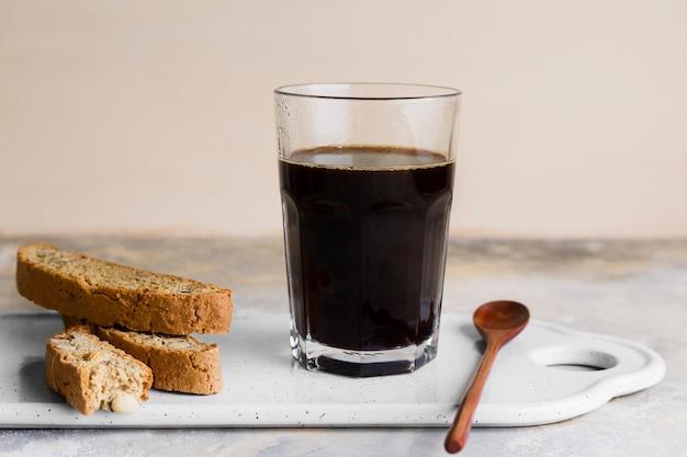 Café preto ao lado de pão com sementes