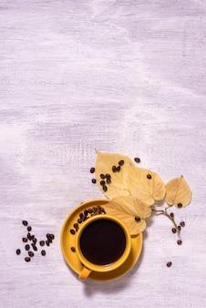 Café preto aromático quente americano em uma velha mesa de madeira com grãos de café e folhas de outono
