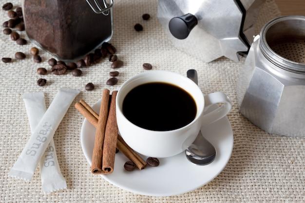 Café preto com bule de café italiano, feijão e canela