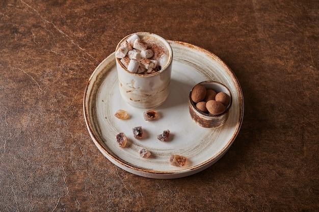 Café preto com espuma de leite e marshmallow em copo leve no prato próximo a açúcar caramelizado e nozes