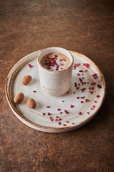 Café preto com framboesas sublimadas em uma caneca leve de cerâmica no prato perto de grãos de cacau doces em
