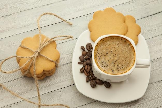 Café preto com grãos de café e biscoitos em um fundo de madeira, conceito de bom dia