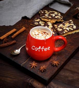 Café preto com marshmallow em uma caneca de cerâmica vermelha