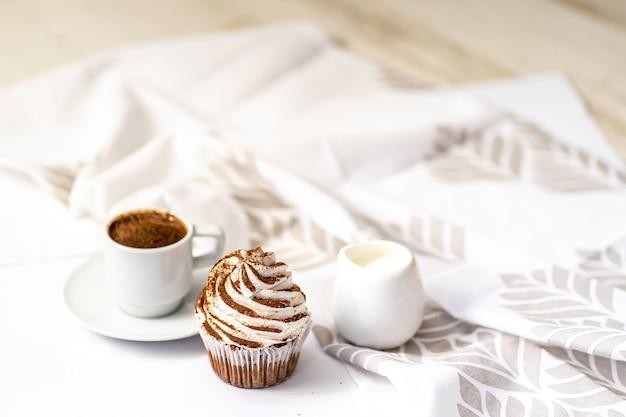 Café preto com muffins de cupcakes sobre uma toalha de mesa branca em uma mesa de madeira