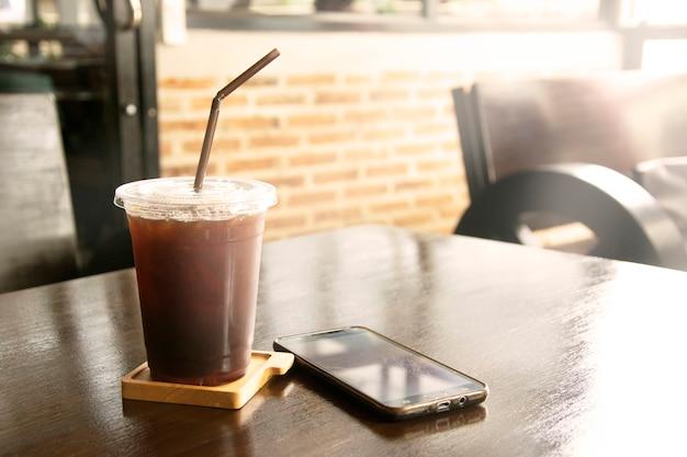 Café preto congelado com palha no copo plástico na tabela.