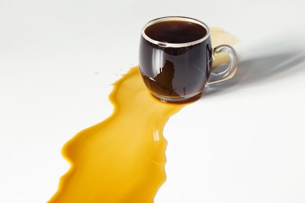 Café preto derramado na mesa branca