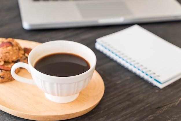 Café preto e biscoitos com laptop e livro de nota