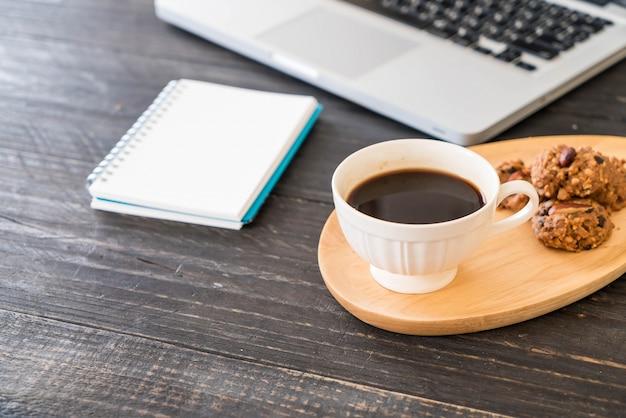 Café preto e biscoitos com laptop e livro de notas