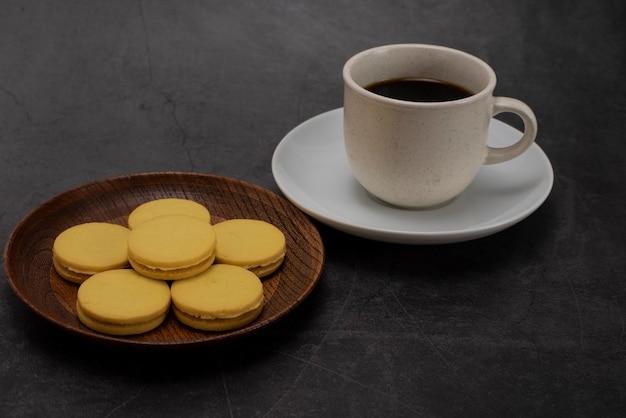Café preto e biscoitos em um fundo escuro